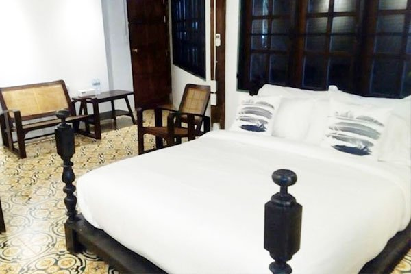 white bedding on teak wooden bed