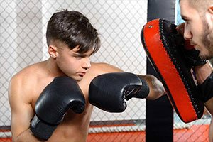 young man muay thai boxing pads